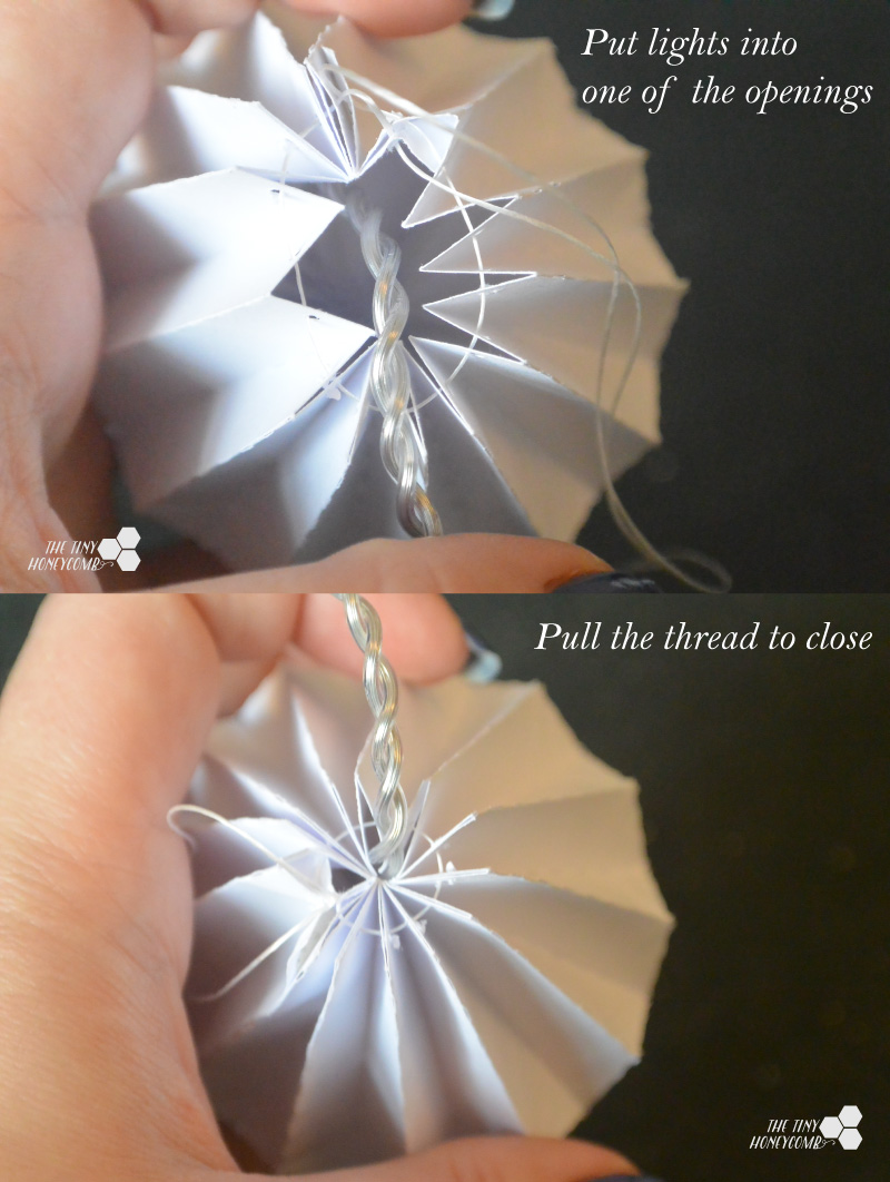 attaching the lights to the origami balls